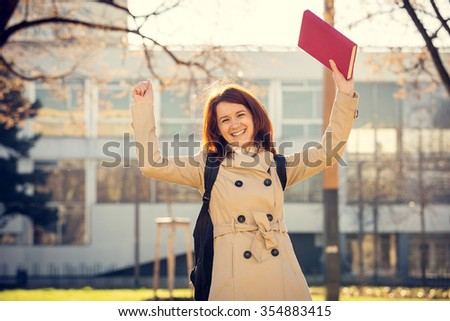 Excited smiling student professional outdoors  holding a red book.University.Smiling young student girl holding a book on a university background .