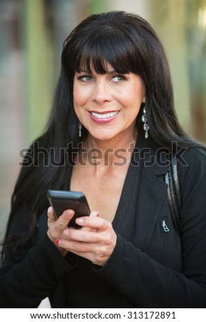 Excited smiling woman using her phone outdoors