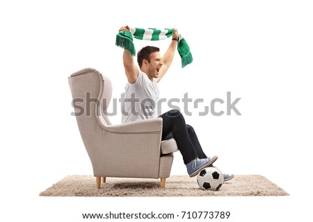 Excited soccer fan with a football and a scarf seated in an armchair cheering isolated on white background