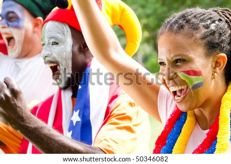 excited soccer fans watching a game - stock photo