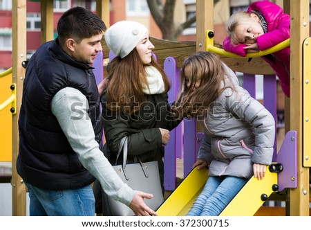 Excited spanish parents with two daughters playing at children's slide - stock photo