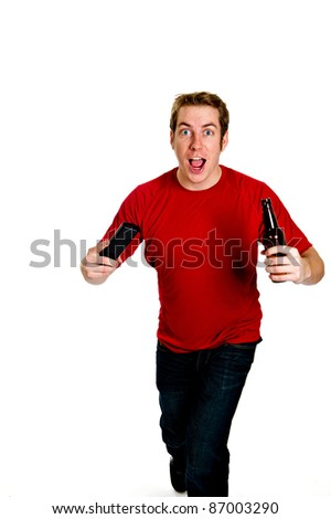 Excited sports fan in a red shirt and jeans, holding a beer in one hand and a TV remote control in the other, watching the big game.  Studio shot isolated on white. - stock photo