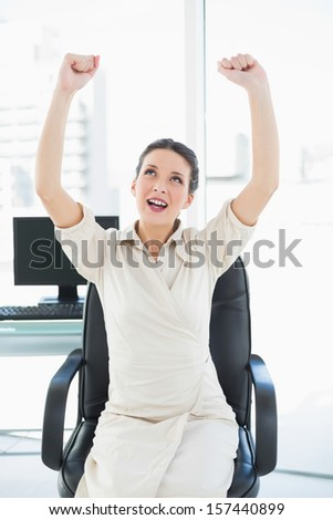 Excited stylish brunette businesswoman raising her arms in bright office