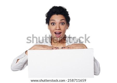 Excited surprised african american business woman standing behind blank white banner, over white background - stock photo