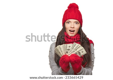 Excited surprised winter woman showing fan of us dollar money in hand, over white background, with copy space - stock photo
