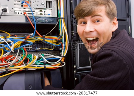Excited technician next to network servers rack