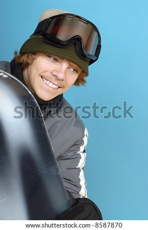 Excited teenager with a snowboard, dressed in winter clothes