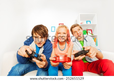 Excited teens hold joysticks and play game console - stock photo