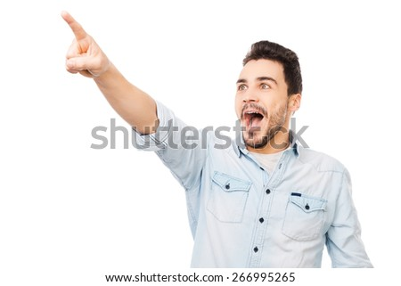 Excited to see your product. Surprised young man pointing away and smiling while standing against white background - stock photo