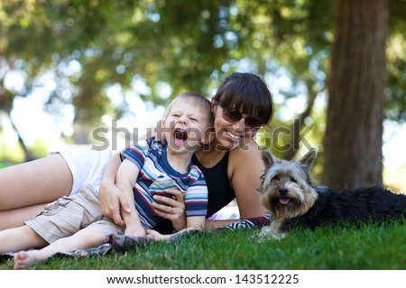 Excited toddler with his mother and dog in a park - stock photo