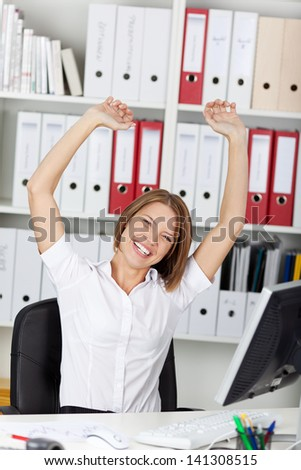 Excited triumphant woman rejoicing raising her arms in the air and laughing and cheering in her office - stock photo