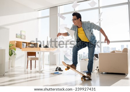 Excited Vietnamese skateboarder performing a trick in his room - stock photo