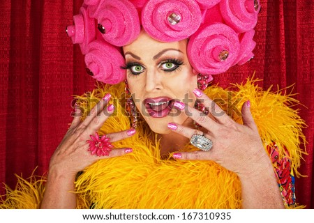 Excited white male drag queen in yellow boa - stock photo