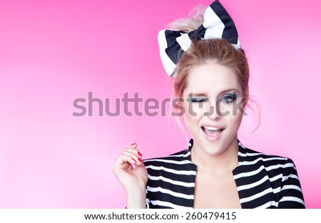 Excited winking young attractive woman on pink background - stock photo