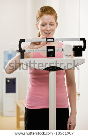 Excited woman checking dieting success by weighing herself on scale - stock photo
