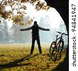 Excited woman cyclist standing in a park with hands outstretched embracing vitality freedom. Outdoor - stock photo