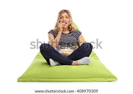Excited woman eating popcorn seated on a green beanbag and looking at the camera isolated on white background - stock photo