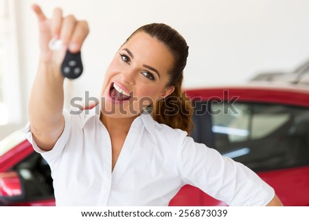 excited woman holding new car key at vehicle dealership - stock photo