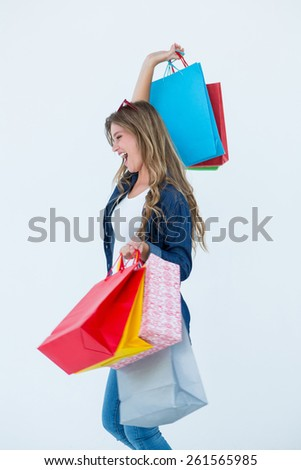 Excited woman holding some shopping bags on white background - stock photo