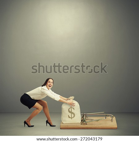 excited woman in formal wear reaching her arms to take bag with money in big mousetrap over dark grey background with empty copyspace overhead - stock photo