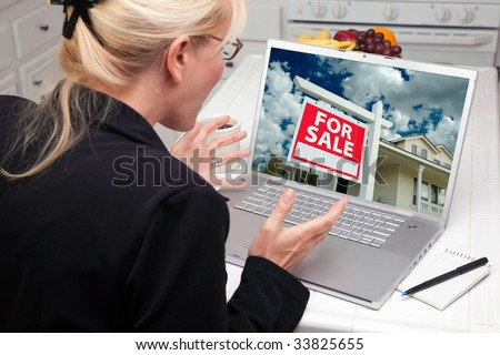 Excited Woman In Kitchen Using Laptop to Buy a Home. Screen image can easily be replaced using the included clipping path. - stock photo