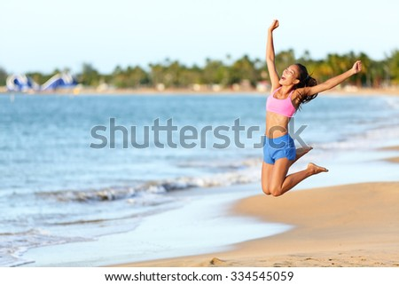 Excited woman jumping at beach. Cheerful female in sportswear is enjoying on shore. Runner with arms raised screaming in midair on sunny day. - stock photo