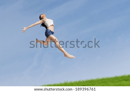 Excited woman jumping highly on the nature