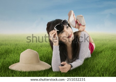 Excited woman lying on meadow. shot outdoors on summertime - stock photo