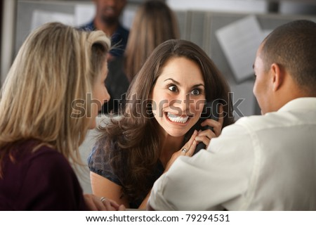 Excited woman office worker with colleagues on phone - stock photo