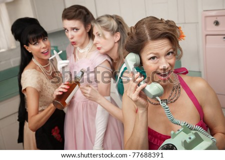 Excited woman on phone while friends drink and smoke in the kitchen - stock photo