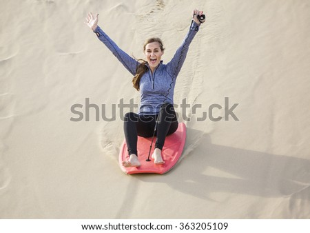 Excited Woman Playing in the Sand Dunes Outdoor Lifestyle - stock photo