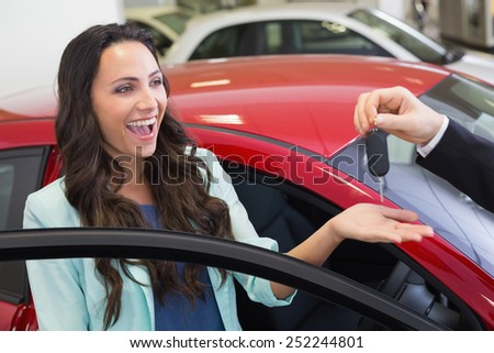Excited woman receiving car key at new car showroom - stock photo