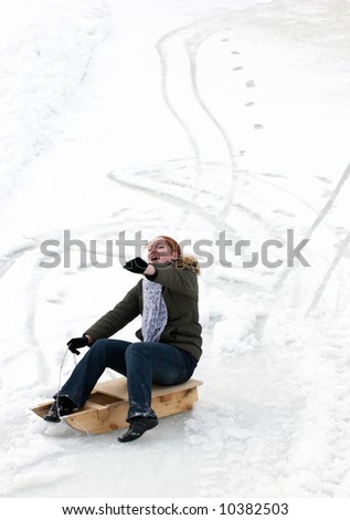 Excited woman, sliding downhill on a sledge.