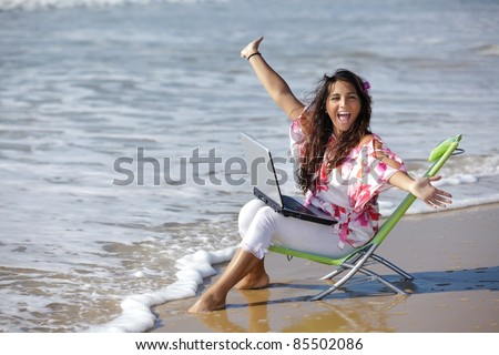 excited woman  using laptop on wild beach - stock photo