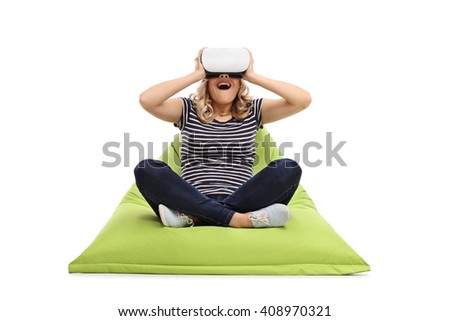 Excited woman using VR goggles seated on a green beanbag isolated on white background
