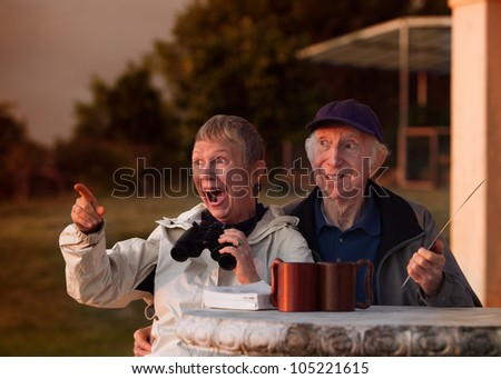 Excited woman with binoculars with and man in hat - stock photo