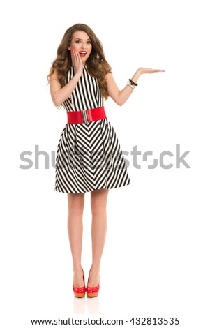Excited woman with long brown hair in black and white striped dress and high heels holding hand on chin, presenting and looking at camera, Full length studio shot isolated on white. - stock photo