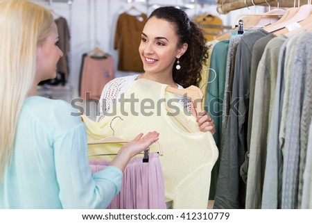 Excited women buying pullover and skirt at the apparel store