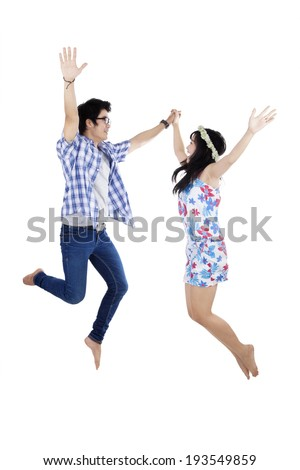 Excited young asian couple having fun while jumping. Isolated on white background - stock photo