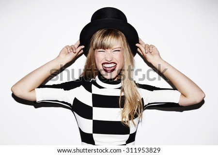 Excited young blond woman in top hat, portrait - stock photo