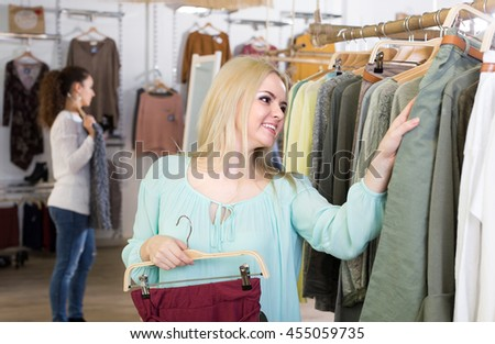 Excited young blondie shopping at the apparel store and smiling