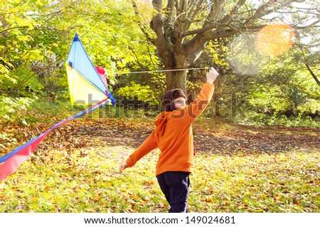 Excited young boy running and flying a colorful kite while in a forest park during the fall with changing color leaves in yellow, orange, red and green during a sunny autumn day.