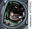 Excited young boy sitting in a tank at an army open house. - stock photo