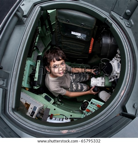 Excited young boy sitting in a tank at an army open house.