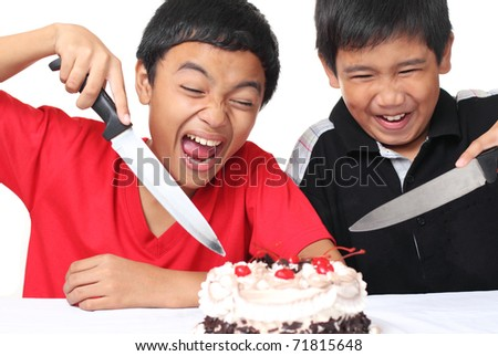 Excited young boys ready to slice a cake - stock photo