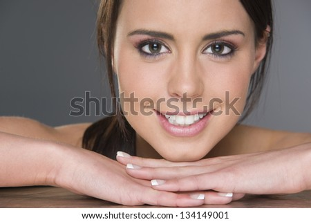 Excited Young Brunette Female Resting Head on Hands Looking at the Camera in Close up Headshot - stock photo