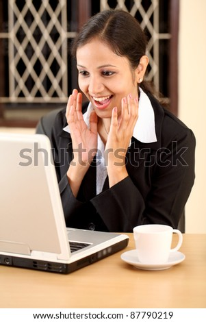 Excited young business woman with laptop - stock photo