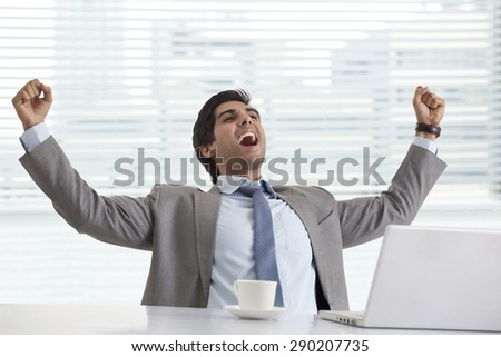 Excited young businessman at his desk celebrating success - stock photo