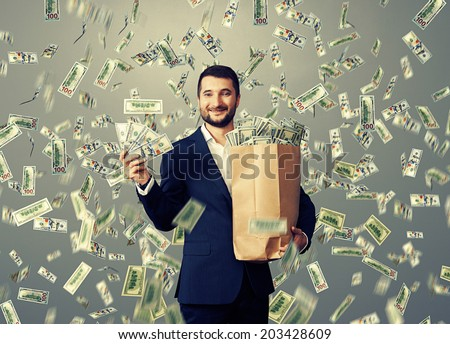 excited young businessman standing under dollar's rain, holding big paper bag and showing money - stock photo