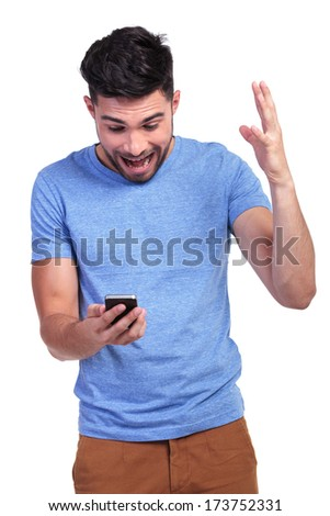 excited young casual man looking shocked by the good news he is reading on his phone - stock photo